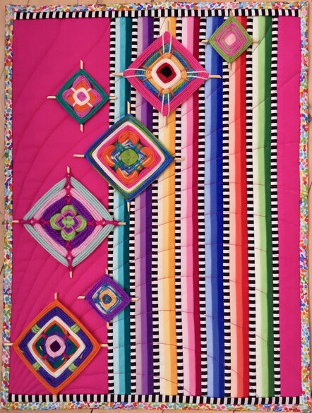 Pink textile art with Ojo de Dios, by Taranaki quilter Christine MacDonald